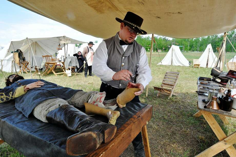 Civil War sawbones:Jonathan Hawkins, playing Confederate surgeon Dr. Harvey Black, discusses the common   practice of limb amputation in the field hospitals of the war. Re-enactors and spectators   converged on Spotsylvania (Va.) Courthouse to commemorate the 150th anniversary of the Battle of the Wilderness. Photo: Brandon Payne, Associated Press