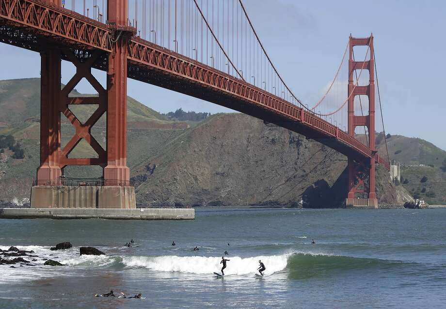 Swell time under the span:Surfers ride a wave near Fort Point below the Golden Gate Bridge in San Francisco. Photo: Eric Risberg, Associated Press