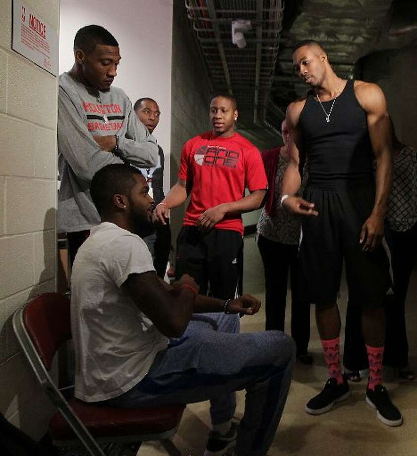 Rockets center Dwight Howard, right, chats with guard Troy Daniels, lower left, as forward Robert Covington, upper left, and guard Isaiah Canaan, center, look on during the teams exit interviews on Monday at the Toyota Center. Photo: James Nielsen, Houston Chronicle
