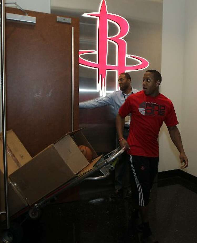 Isaiah Canaan prepares to leave as Rockets media relation's Ryan Bradford holds a door for the point guard. Photo: James Nielsen, Houston Chronicle