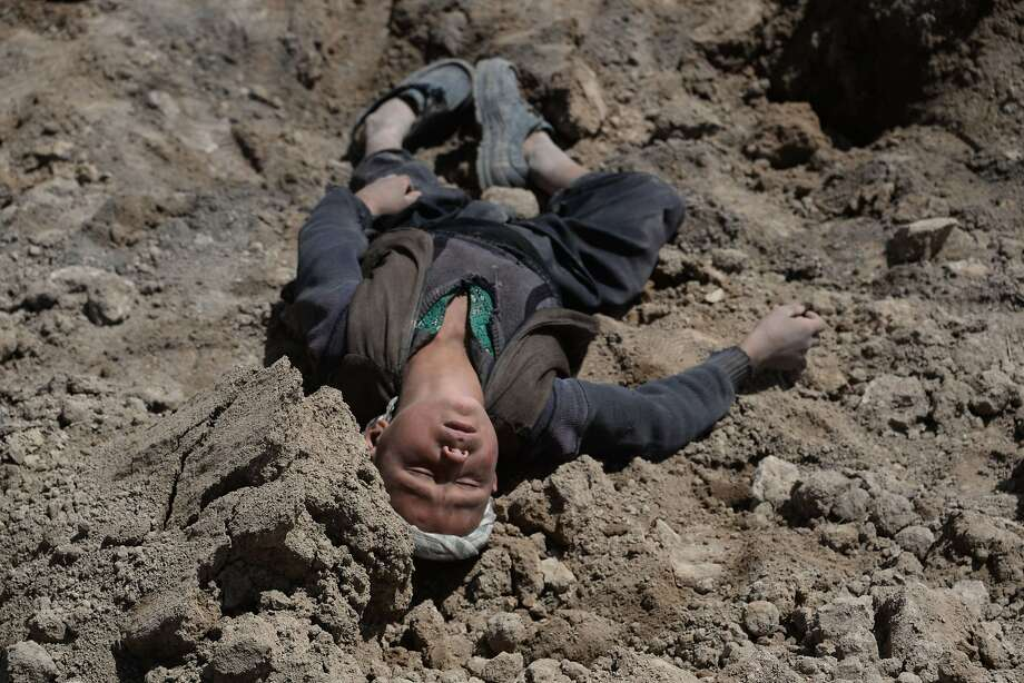 Orphaned by disaster:An Afghan boy lies in the dirt as he grieves for his family at the site 