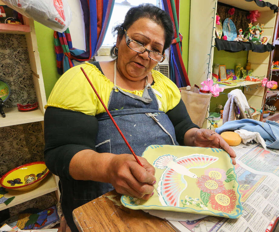 Grace Gonzales paints a fanciful hummingbird on a clay plate at the MujerArtes cooperative's workshop at La Casita, 1412 El Paso St. Photo: Photos By Marvin Pfeiffer / Southside Reporter / Express-News 2014