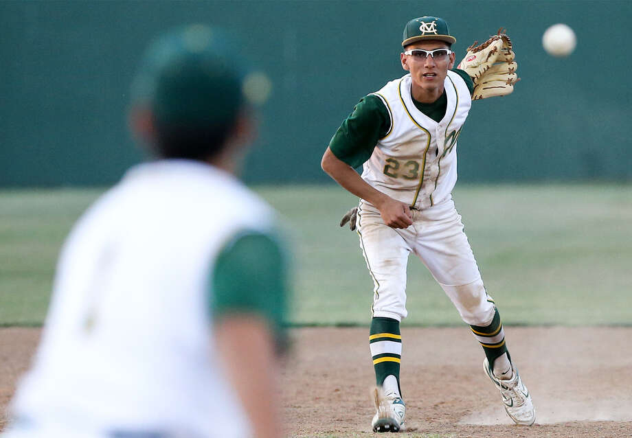 McCollum's Hector Arevalos watches his throw to first base during the third inning of their 5A bidistrict playoff with Gregory- Portland at Tejeda Stadium on Friday. G-P won the series. Photo: Marvin Pfeiffer / Southside Reporter / EN Communities 2014