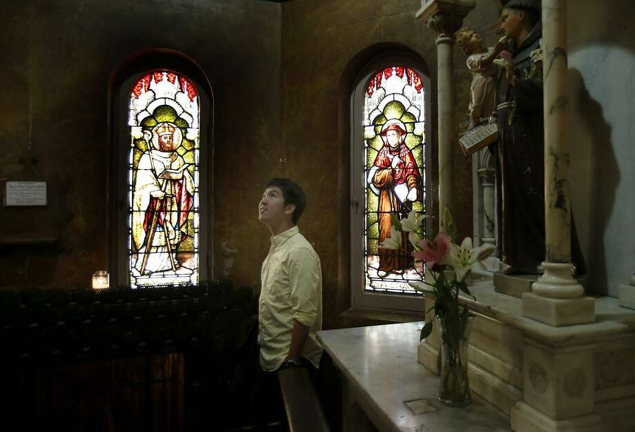 St. Boniface volunteer Lucas Chan visits a shrine. At left is a stained glass window that was stolen. Photo: Brant Ward, The Chronicle