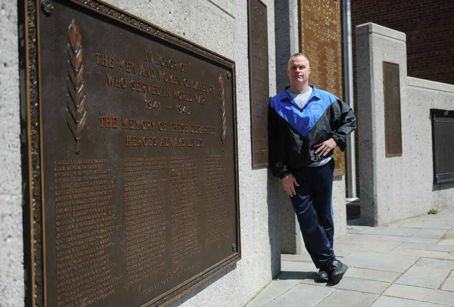 Director Dan Hayes poses by the World War II plaque outside the Danbury War Memorial in Danbury, Conn. Monday, May 5, 2014. A three-member subcommittee of the City Council voted unanimously in early June to waive the fees, which is expected to save the struggling Memorial $4,000 to $6,000. Photo: Tyler Sizemore / The News-Times