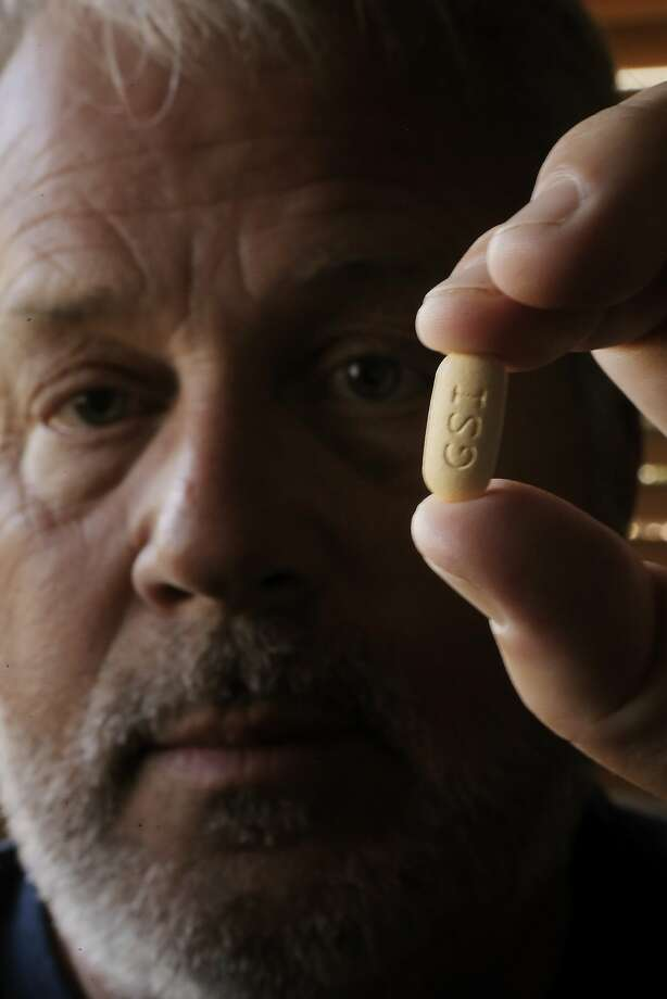 Scott Barnes holds a pill of Sovaldi in his San Luis Obispo, Calif., home on Wednesday, April 30, 2014. Barnes is a Vietnam War army veteran who suspects he caught hepatitis C (before it was known by that name) toward the end of the war (1973) but wasn't officially diagnosed until the 2000s. He was able to convince his VA doctors to help him get on a regimen of Sovaldi, a drug developed by Gilead Sciences, which is hailed as a cure for hepatitis C. He has stage IV hep C, and sees this treatment as his last chance. Photo: Carlos Avila Gonzalez, The Chronicle