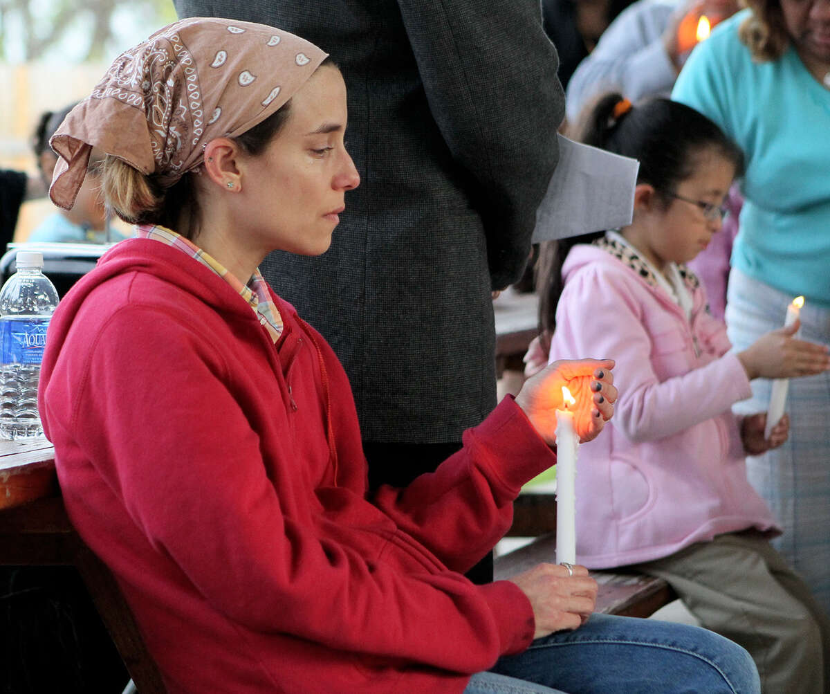 Rister Vasquez sheds a tear while holding a candle as residents of Mission Trails gather to pray April 16.