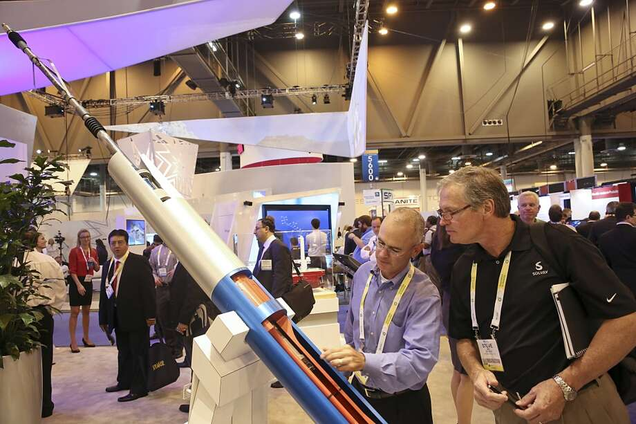 From left to right, Brian Stern and Steve King with SOLVAY look at a wireless pipe rover system made by Superior Energy Services on May 5, 2014 in the NRG Center in Houston, TX. (Photo: Thomas B. Shea/For the Chronicle) Photo: Thomas B. Shea, For The Chronicle