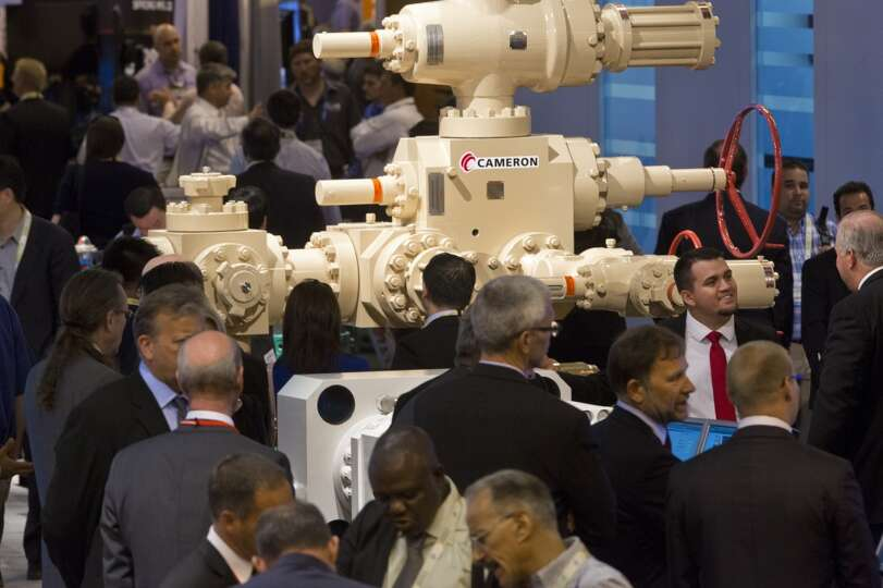 Offshore Technology Conference visitors gather around the Cameron booth, a flow equipment products c