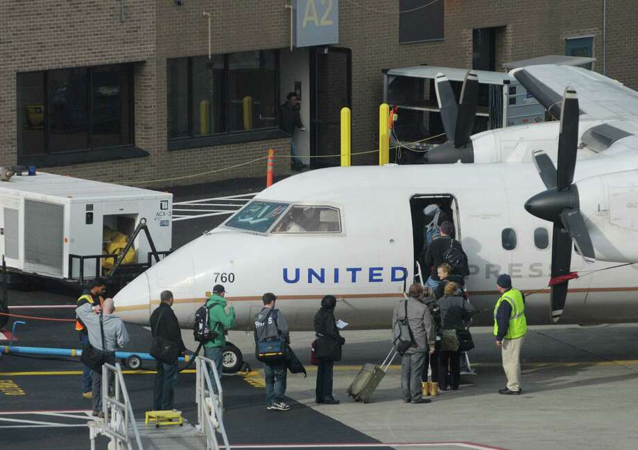 Passengers make their way onto a United Express flight about to take off at the Albany International Airport on Sunday, Nov. 25, 2012 in Colonie, NY.  (Paul Buckowski / Times Union) Photo: Paul Buckowski / 00020229A