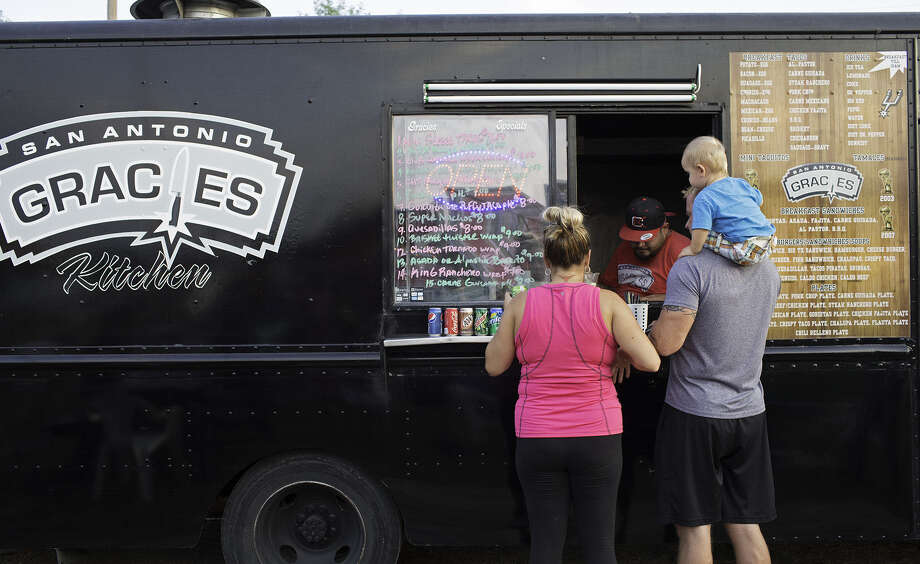 "Felicia, Gary and son Chase Armstrong place their orders at Gracie's Kitchen food truck at a ""Boardwalk on Bulverde"" event in August 2013. The Food Truck Roundup in Cibolo May 10 will feature similarly served cuisine. Photo: Express-News File Photo / THE SAN ANTONIO EXPRESS-NEWS"