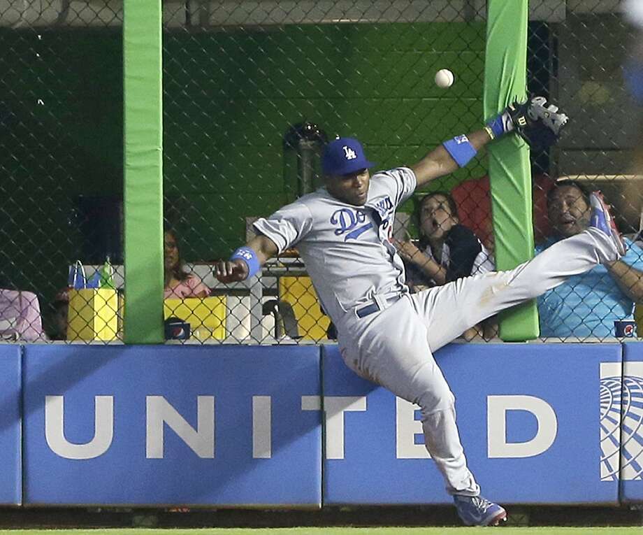 Yasiel Puig collides with the fence while attempting a ninth-inning catch Sunday. Photo: Wilfredo Lee, Associated Press