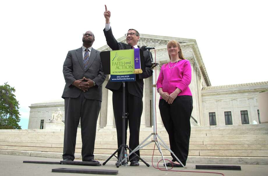 Rev. Dr. Rob Schenck, of Faith and Action, center, speaks in front of the Supreme Court with Raymond Moore, left, and Patty Bills, both also of Faith and Action, during a news conference, Monday, May 5, 2014, in Washington, in favor of the ruling by the court's conservative majority that was a victory for the town of Greece, N.Y., outside of Rochester. A narrowly divided Supreme Court upheld decidedly Christian prayers at the start of local council meetings on Monday, declaring them in line with long national traditions though the country has grown more religiously diverse. (AP Photo/Carolyn Kaster) Photo: Carolyn Kaster, STF / AP