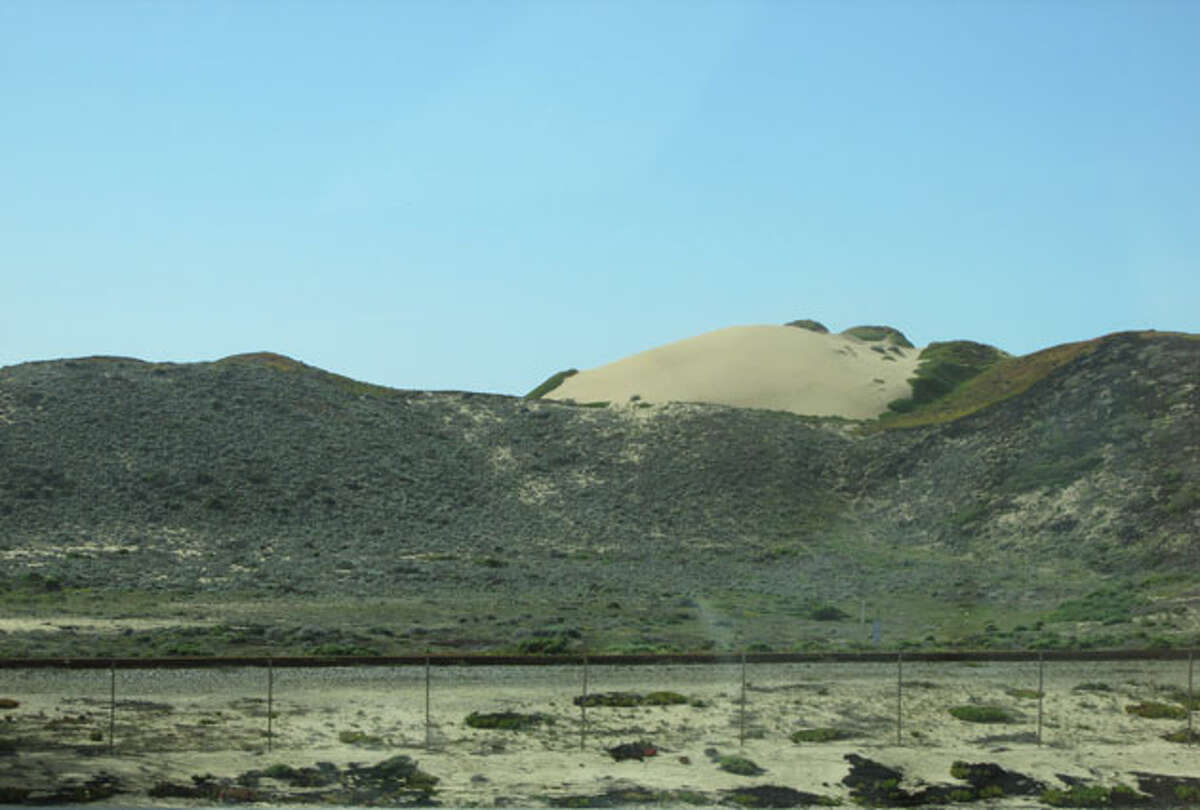 Sand dunes by the side of the road . These can be seen all along California Highway 1 on the way in to Monterey.