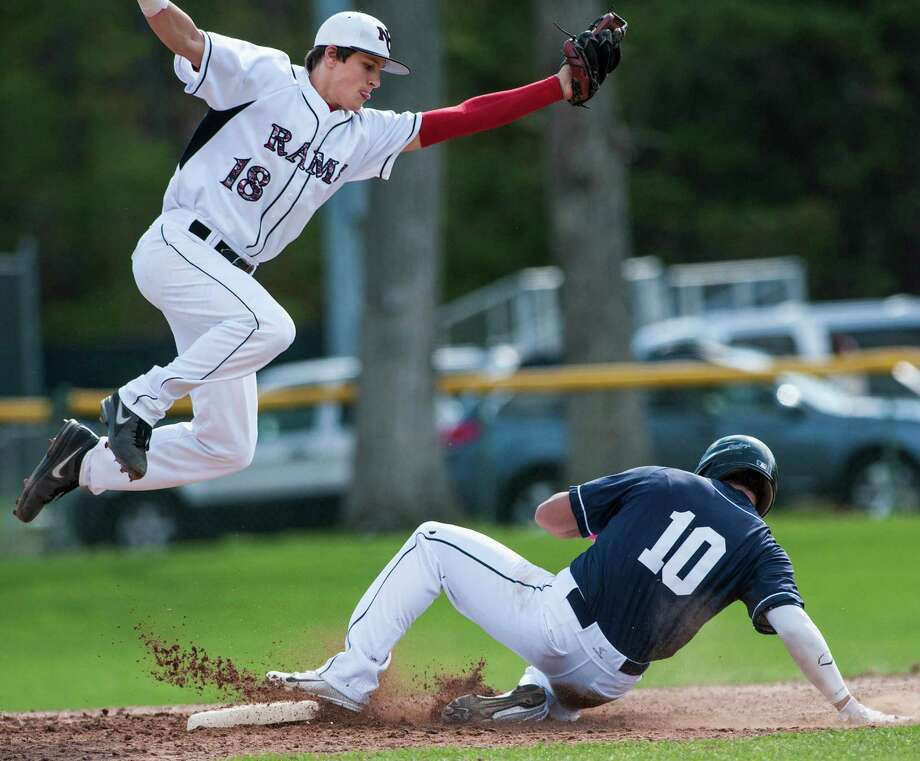 Staples high school Topher Brown slides into second safely as New Canaan high school second baseman Brandon Abate jumps to catch to throw during a baseball game played at Mead Park, New Canaan, CT on Monday, May, 5th, 2014. Photo: Mark Conrad / Connecticut Post Freelance