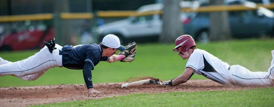 Staples high school second baseman Nick Vega dives as he tries to tag New Canaan high school's Zack Smith out at second during a baseball game played at Mead Park, New Canaan, CT on Monday, May, 5th, 2014. Photo: Mark Conrad / Connecticut Post Freelance