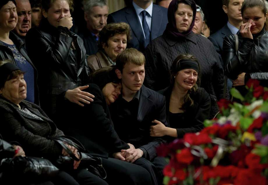 """Mourners and family members cry next the coffin of regional parliament member Vyacheslav Markin, in Odessa, Ukraine, Monday, May 5, 2014.  Markin, who was known for speaking out against the government in Kiev, was buried on Monday while about 300 pro-Russian supporters shouted """"Hero, hero!"""" Markin died Sunday from burn wounds sustained in Friday's fire.(AP Photo/Vadim Ghirda) Photo: Vadim Ghirda, STR / AP"""