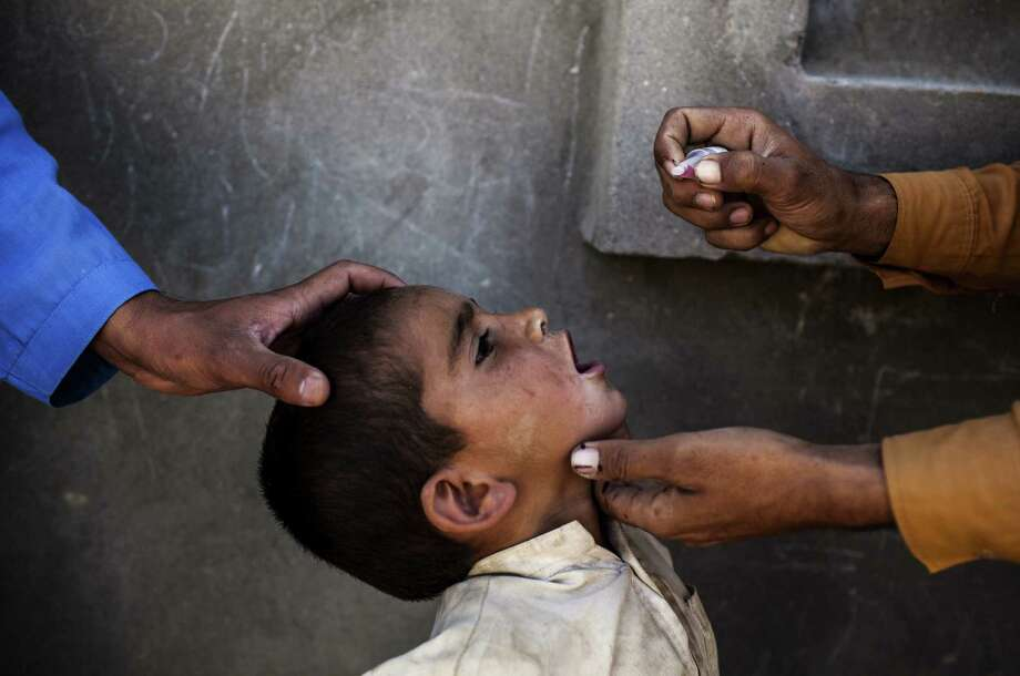 Health workers vaccinate a child for polio in Afghanistan, where the highly contagious virus spread from Pakistan. Photo: Diego Ibarra Sanchez / New York Times / NYTNS