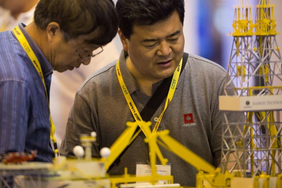 Yue Jixiang, center, and Qi Yaoguang, left, take a look at a  Bassoe Technology BT-UDS Ultra Deepwater Drillship at the 2014 Offshore Technology, Monday, May 5, 2014, in Houston. The BT-UDS is 227.57 meters in length. ( Marie D. De Jesus / Houston Chronicle ) Photo: Marie D. De Jesus, Houston Chronicle