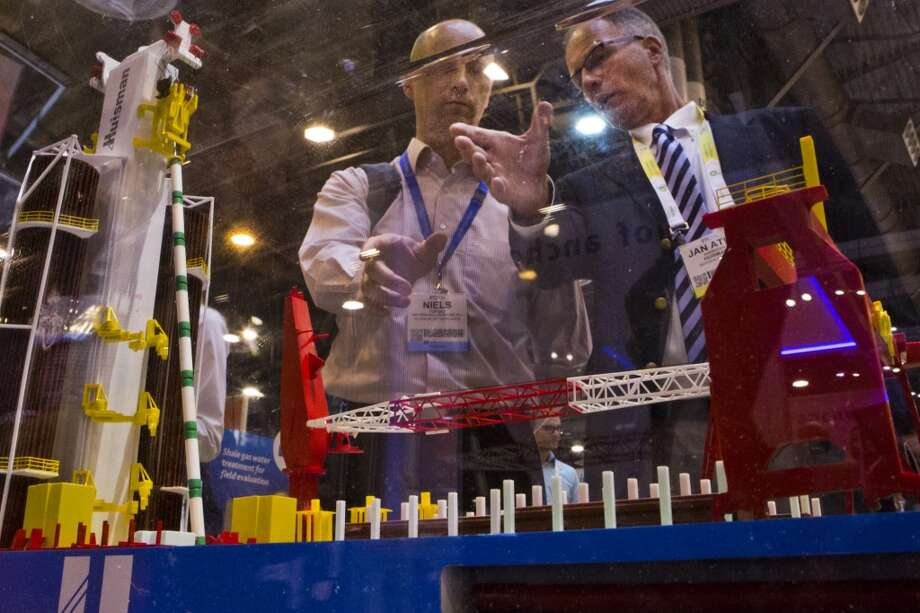 Jan Atle Andresen, right, of Huisman Equipment shows the Huisdrill 12000 drill ship to Niels Torgau at the Huisman Equipment booth during the first day of the 2014 Offshore Technology Conference, Monday, May 5, 2014, in Houston. ( Marie D. De Jesus / Houston Chronicle ) Photo: Marie D. De Jesus, Houston Chronicle