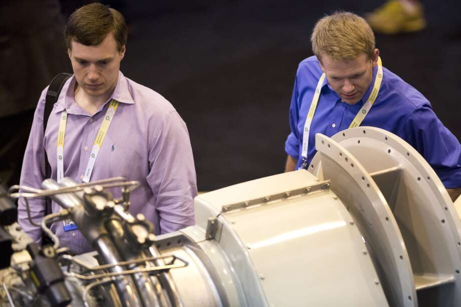 Thomas Williams, left, and Gregory Armstrong, right, both with aeronautical engineers backgrounds take admire a Caterpillar Solar Turbines at the Offshore Technology Conference, Monday, May 5, 2014, in Houston. ( Marie D. De Jesus / Houston Chronicle ) Photo: Marie D. De Jesus, Houston Chronicle