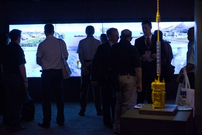 Offshore Technology Conference visitors gather to watch an informational video on offshore drilling