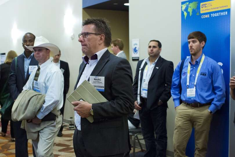 Offshore Technology Conference goers listen through speakers to Dr. Facheng Wang from outside the al
