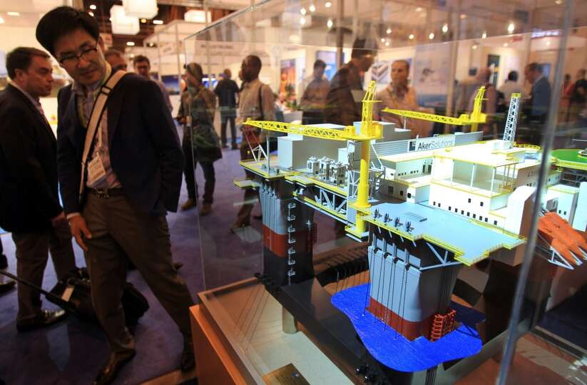 Attendees view a small scale model of an offshore platform in the Aker Solutions booth during the Of