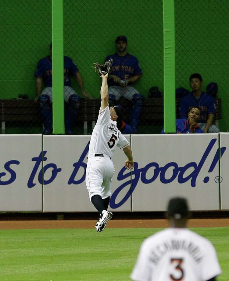 Miami Marlins left fielder Reed Johnson (5) catches a fly ball hit by New York Mets' Omar Quintanilla during the fifth inning of a baseball game in Miami, Monday, May 5, 2014. (AP Photo/Alan Diaz) ORG XMIT: FLAD109 Photo: Alan Diaz / AP