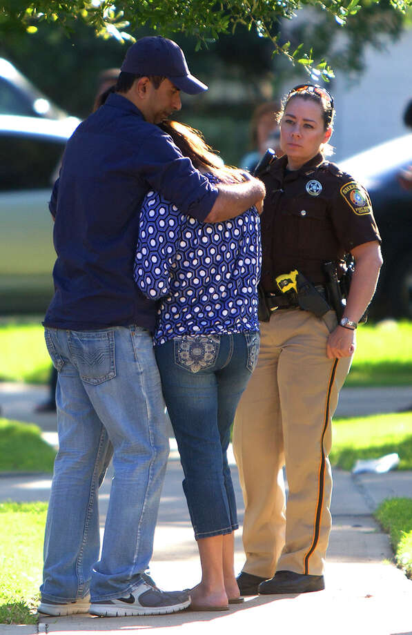 "Mourners react to the news Monday that a couple was fatally shot and their children, 11 and 15, injured at a home in the 4800 block of Russett Lane, southwest of Sugar Land. Neighbors were stunned by the shootings of a family they called ""normal"" and ""happy."" Photo: Cody Duty, Staff / © 2014 Houston Chronicle"
