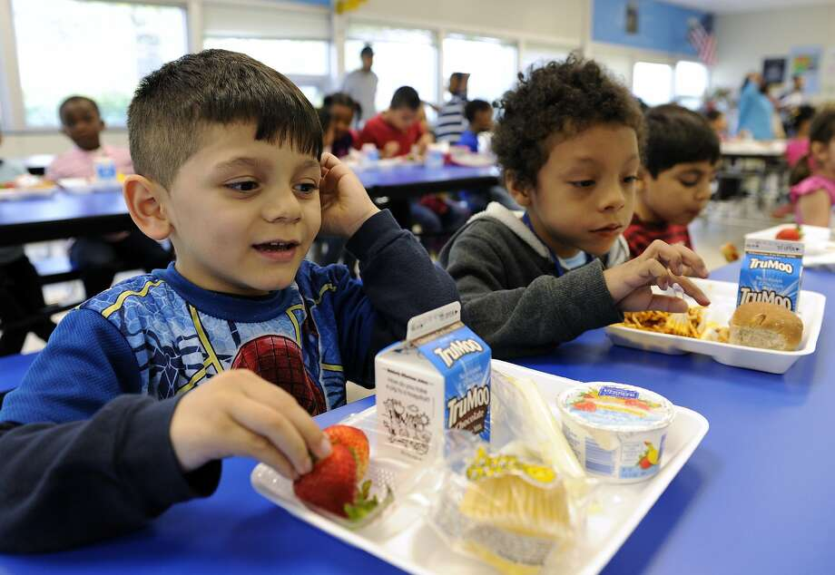 Biden Arias-Romers (left) and Nathaniel Cossio-Boatwright eat lunch at Patrick Henry Elementary in Alexandria, Va. The nutrition director says the whole-grains switch has been difficult. Photo: Susan Walsh, Associated Press