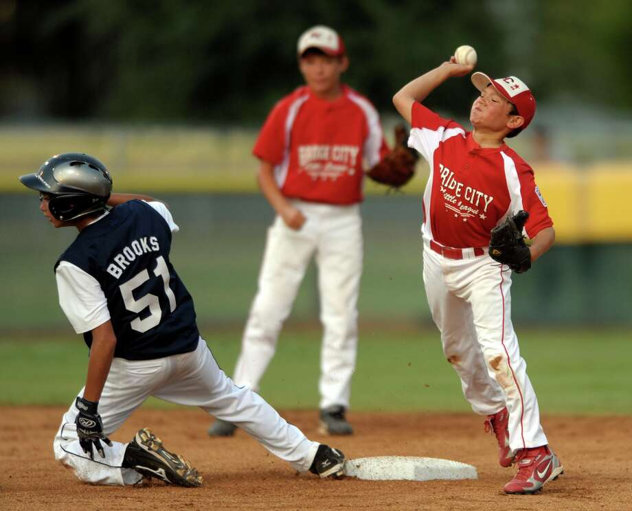 Dillon Taylor of Bridge City Little League unsuccessfully attempts to turn a double play as Drew Brooks of McAllister Park slides in during Little League action in Waco on Thursday, Aug. 13, 2009.  Photo: BILLY CALZADA / Beaumont