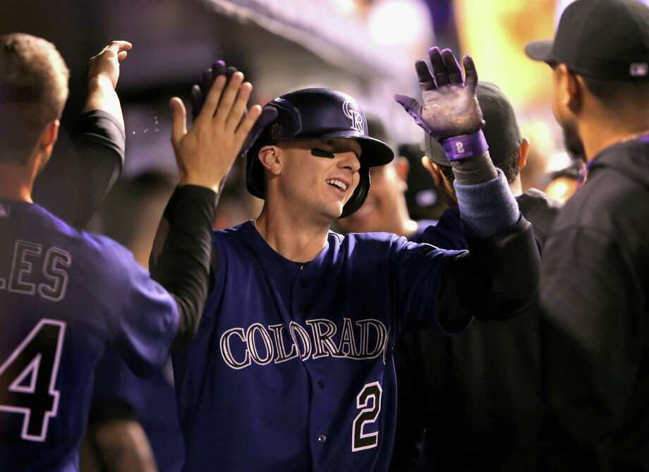 Troy Tulowitzki is the center of attention in the Colorado dugout after hitting a two-run homer in the seventh inning of the Rockies' 8-2 victory over Texas at Coors Field on Monday night. Photo: Doug Pensinger, Staff / 2014 Getty Images