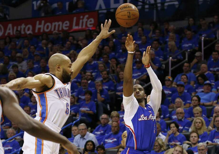 Clippers guard Chris Paul, who hit a career-best eight 3-pointers, shoots over Thunder guard Derek Fisher. Paul finished with 32 points in a Game 1 victory. Photo: Sue Ogrocki / Associated Press / AP