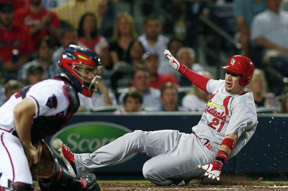 Cardinals right fielder Allen Craig (right) scores on a Peter Bourjos base hit during the sixth inning. Photo: John Bazemore / Associated Press / AP
