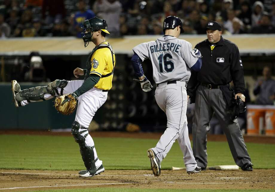 Mariners outfielder Cole Gillespie scores past A's catcher John Jaso after a single by Seattle's Brad Miller in the sixth inning. Photo: Marcio Jose Sanchez, Associated Press