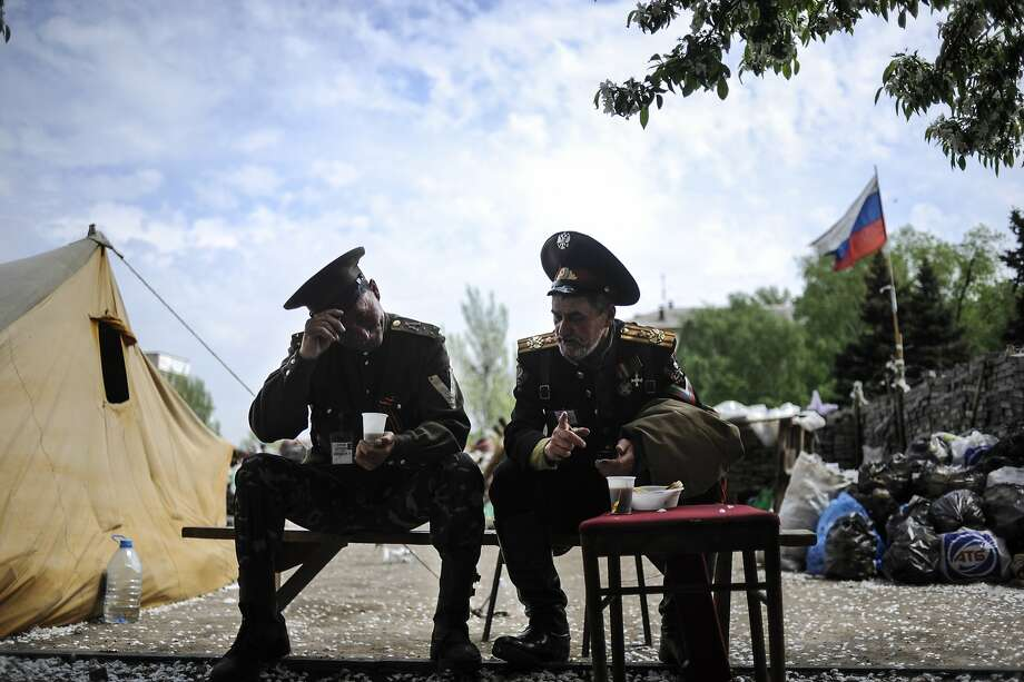 Pro-Russian Cossacks eat a dinner outside the regional administration building in Donetsk, Eastern Ukraine, Monday, May 5, 2014. Pro-Russian forces and their supporters have for a few weeks been seizing and ransacking government buildings across eastern Ukraine amid a mounting anti-government insurgency that is threatening to tip the former Soviet nation into widespread civil conflict. (AP Photo/Evgeniy Maloletka) Photo: Evgeniy Maloletka, Associated Press