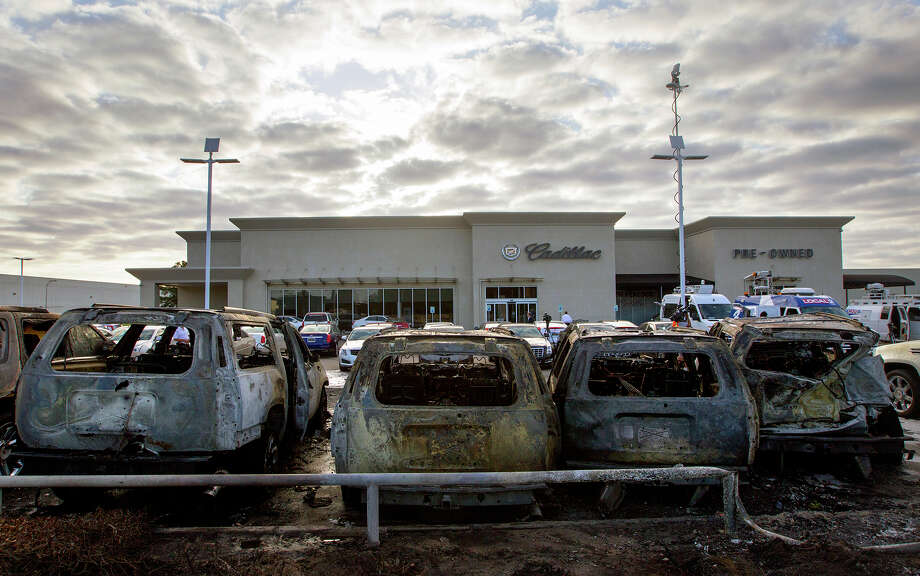 A row of burnt Cadillac Escalades sit at Tom Peacock Cadillac near Airtex, Tuesday, May 6, 2014, in Houston. The vehicles burned to the ground after a wreck sparked a fire igniting the Escalades on the lot. General Manager Steven Hainline said the damage totals nearly $750,000. Photo: Cody Duty, Houston Chronicle / © 2014 Houston Chronicle