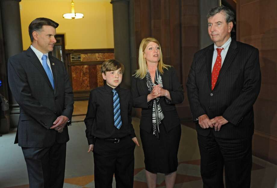10 year-old dog bite victim Frankie Flora, second from left,  holds a press conference outside the senate chambers of the Capitol to advocate for Frankie's Bill with Senator Terry Gipson, left, his mom Maria Flora and Senator Neil Breslin on Monday, May 5, 2014 in Albany, N.Y. The  New York native and 2010 New York Ambassador for the Children's Miracle Network was advocating for the Frankie Flora Law that would hold dog owners accountable for the first time and every time a dog bites someone. (Lori Van Buren / Times Union) Photo: Lori Van Buren, Albany Times Union