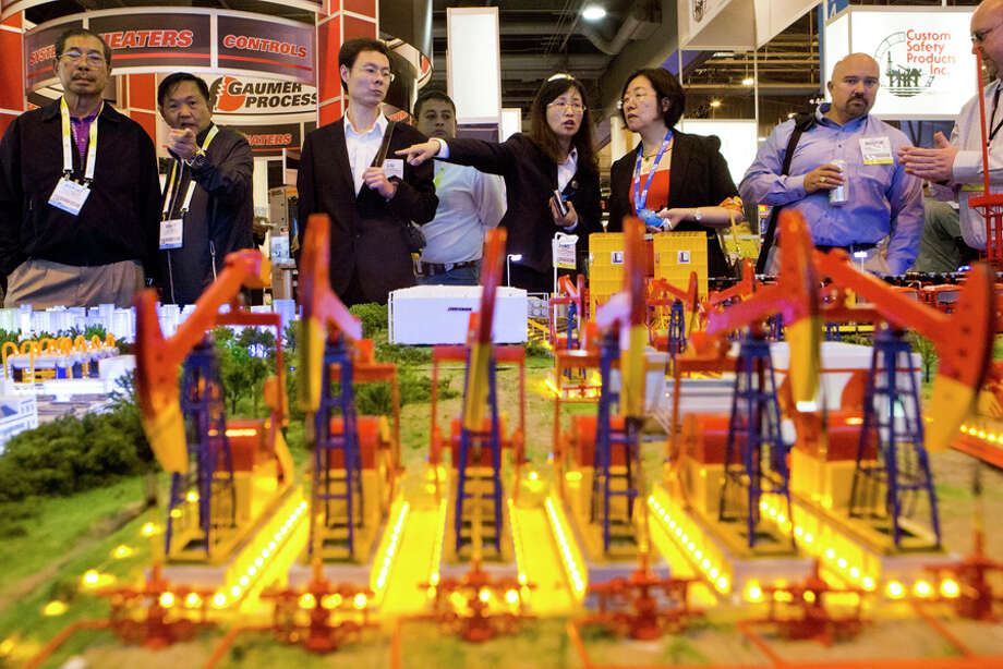 2014 Offshore Technology Conference visitors stop at the China Petrochemical Corporation (Sinopec Group) booth to take a look at the oversized model during the second day of the conference at the NGR Center, Tuesday, May 6, 2014, in Houston. ( Marie D. De Jesus / Houston Chronicle ) Photo: Marie D. De Jesus, Houston Chronicle / © 2014 Houston Chronicle