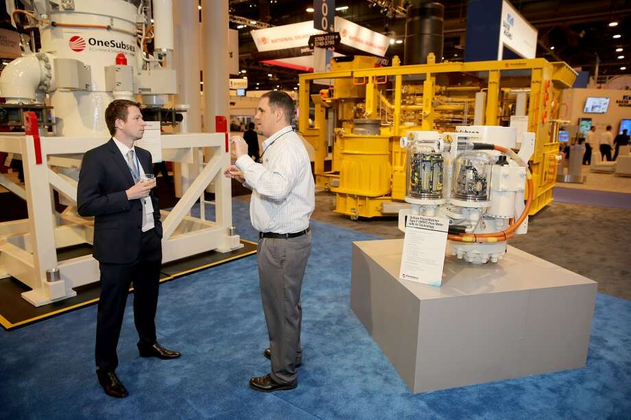 Matt Dogwill with OneSubsea (right) and Joseph Hansen with U.S. Bolt Manufacturing Inc. talk about the possibilities of the OneSubsea Phase Watcher on the floor of the OTC on May 6, 2014 in the NRG Center in Houston, TX. (Photo: Thomas B. Shea/For the Chronicle) Photo: Thomas B. Shea, For The Chronicle