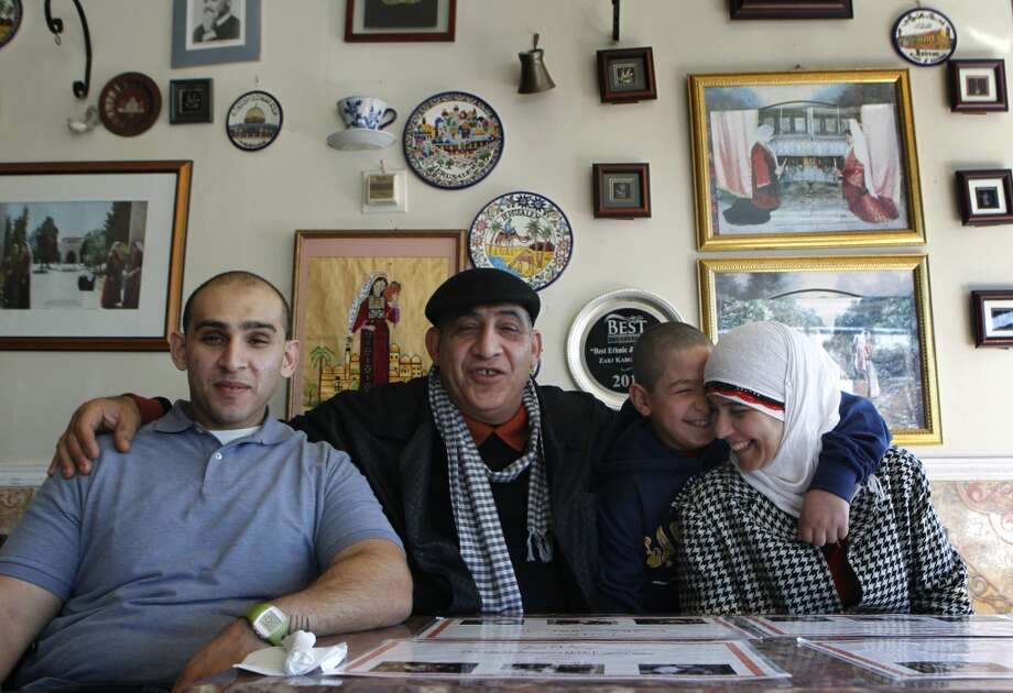 Naime Ayyad and his wife Fayza sit with their sons Ramzy (left)  and Amir at the family's Zaki Kabob House . Photo: Paul Chinn, The Chronicle