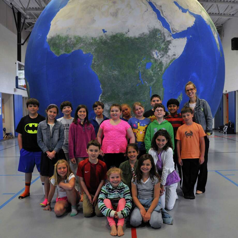 "The 20-foot-high ""Earth Balloon"" recently visited Tokeneke School in Darien. The balloon is an inflatable globe made up of a high-resolution satellite images with true-to-life colors. The students learned about the Earth's continents, oceans, ecosystems, weather and where certain animals live. They even entered, sitting right on Antarctica, while being treated to science presentations. Photo: Contributed Photo, Contributed / Darien News"