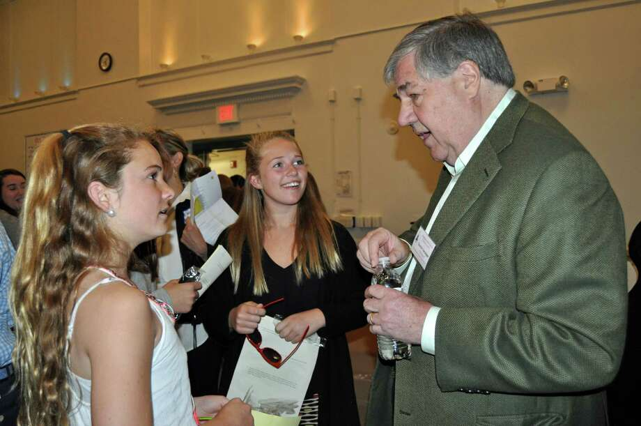 Elizabeth Jennings, left, and Hailey Meier speak with Dennis Swanson after his keynote opening speech at Middlesex Middle School's recent Career Day. Photo: Contributed Photo, Contributed / Darien News