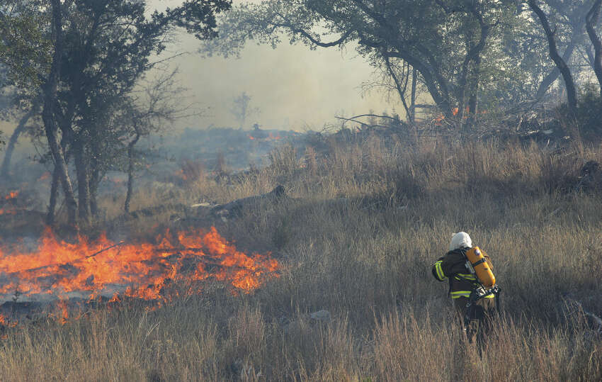 Surrounded by dried grass, a member of the City of Shavano Park Fire Department works a major brush fire in northern Bexar County north of San Antonio on Thursday, Jan. 5, 2006. Residents of the Fossil Ridge subdivision, south of the fire, were asked to evacuate due to the danger. Fire departments from throughout the county were involved in the firefighting effort.