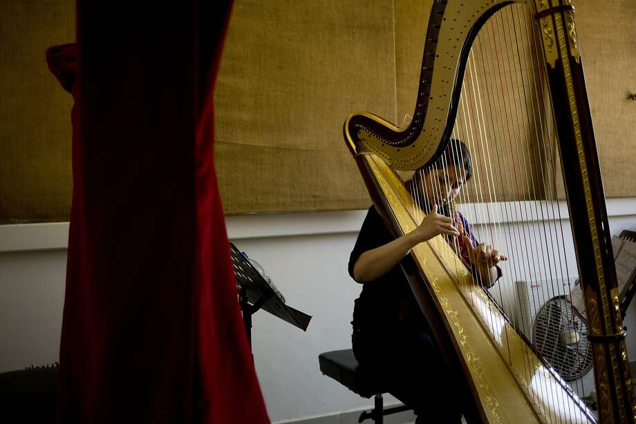A musician plays harp during a practice at an art school that adjoins the Damascus Opera House. Two students were killed when a mortar landed outside the building in April. Photo: Dusan Vranic, Associated Press