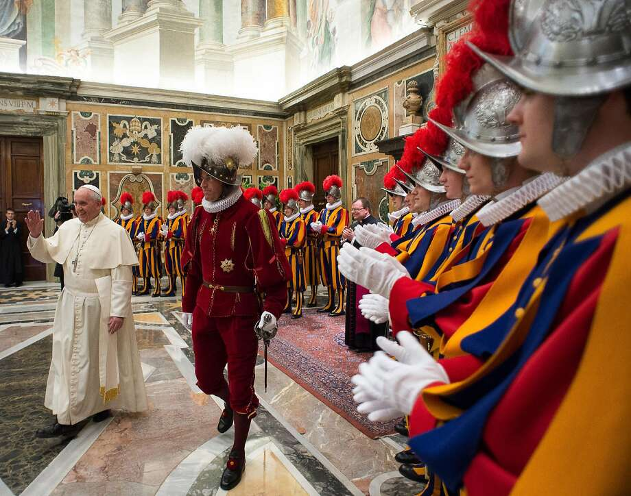 In this photo taken Monday, May 5, 2014, and provided by the Vatican newspaper L'Osservatore Romano, Pope Francis, flanked by Swiss Guards Commander Daniel Rudolf Anrig, greets new Swiss Guards the day before their swearing-in ceremony, as he arrives to meet them in the Clementine hall at the Vatican.  (AP Photo/L'Osservatore Romano) Photo: Associated Press