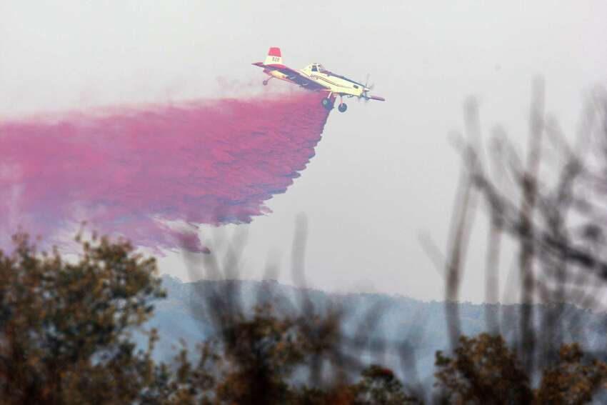 A plane drops fire retardant as several area fire department battle a wildfire at Camp Stanley off Ralph Fair Road, Wednesday, Sept. 7, 2011. The fire forced the evacuation of a small area of Fair Oaks Ranch but was under control by early evening.