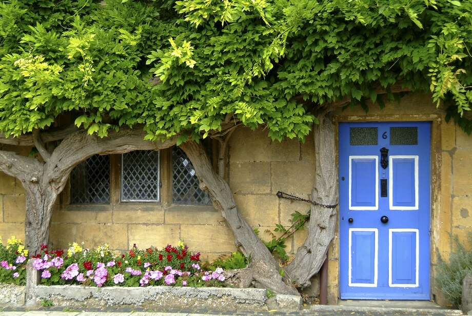 Wysteria surrounds the doorway and window of a pretty limestone cottage in the Cotswold village of Broadway. Photo: Visit Britain