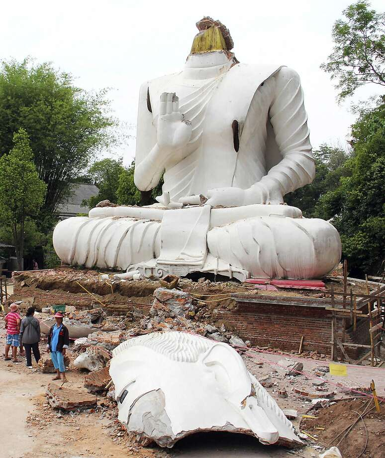 Off with his head:Thai villagers examine the damage after an earthquake in Chiang Rai province decapitated a 